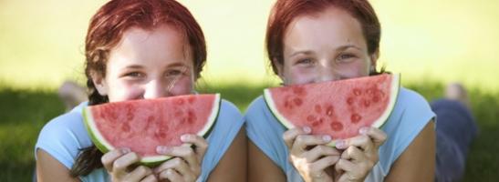 Εικόνα με δύο κοπέλες που κρατούν φέτες καρπουζιού στο πρόσωπό τους. Η εικόνα δείχνει με ποιον τρόπο θα μπορείς να ασχολείσαι με τις αγαπημένες σου δραστηριότητες κατά τη διάρκεια της περιόδου σου αν ακολουθήσεις τις συμβουλές μας για να νιώθεις καλά.