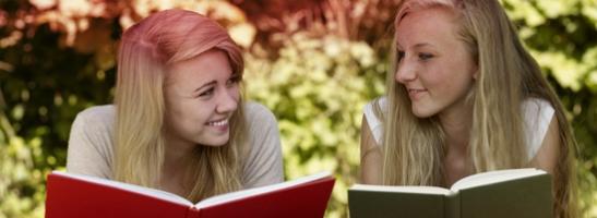Εικόνα με δύο κοπέλες που διαβάζουν ένα βιβλίο. Η εικόνα καταδεικνύει τους πολλούς μύθους που συνδέονται με την εμμηνόρροια.