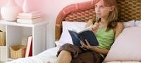 Εικόνα μιας κοπέλας που κάθεται στο κρεβάτι της και κρατάει σημειώσεις. Η εικόνα δείχνει ότι υπάρχουν πολλές ερωτήσεις γύρω από την πρώτη περίοδο, αλλά δεν υπάρχει κανένας λόγος ανησυχίας!